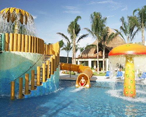 An outdoor pool with raining mushroom umbrellas and waterslide.