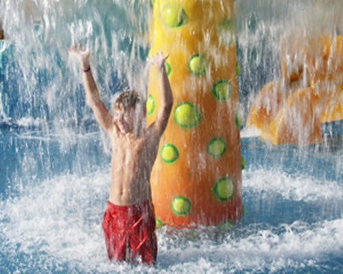 Kid playing at the kiddie pool beneath a raining mushroom umbrella.