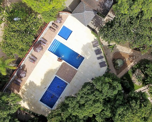 Birds eye view of an outdoor swimming pool with chaise lounge chairs and sunshades.