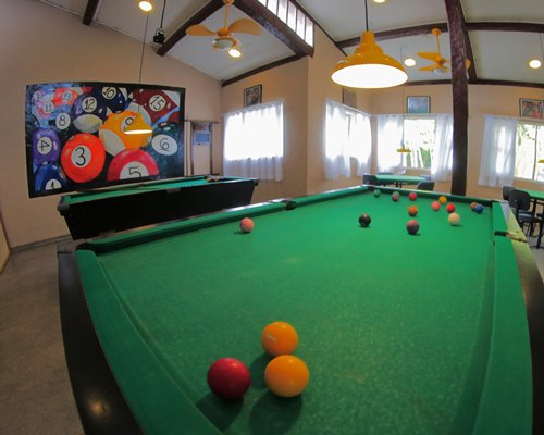 An indoor recreational room with two pool table and television.
