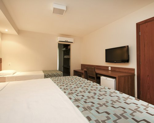 A well furnished bedroom with two twin beds and television.