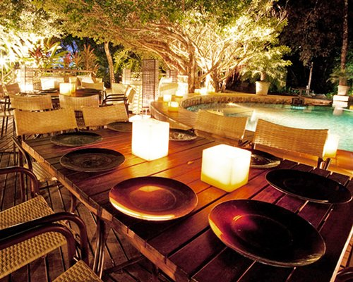 An outdoor fine dining area alongside the outdoor swimming pool at night.