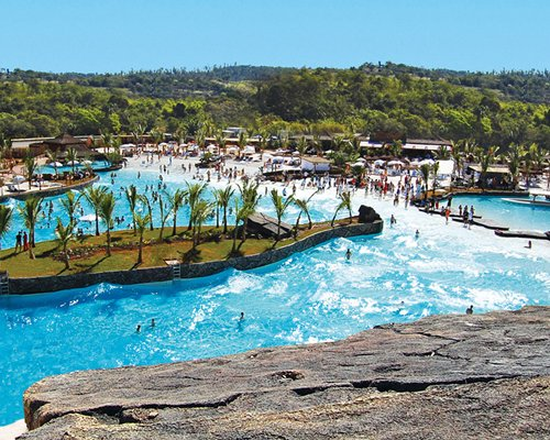 An outdoor wave pool alongside the swimming pool and the resort.