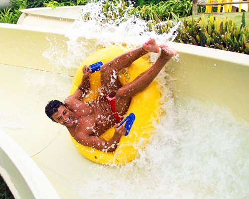 Man on an inflatable water tube sliding at the water park.