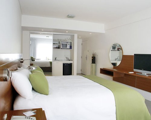 A well furnished bedroom with television and open plan kitchen.