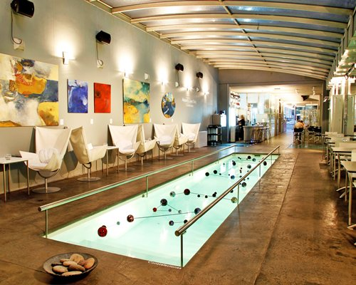An indoor lounge area surrounding a small pool.