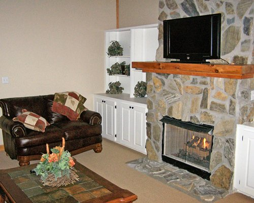 A furnished living room with a love seat television and fire in the fireplace.