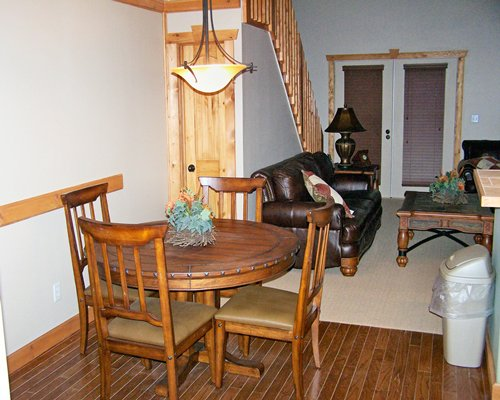A well furnished living room with dining area and stairway.