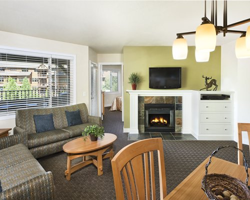 An open plan living and dining area with a fireplace and television.