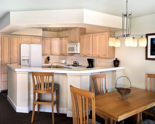 A well equipped kitchen alongside a dining table.