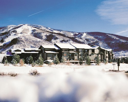 Exterior view of WorldMark Steamboat Springs surrounded by mountains during winter.