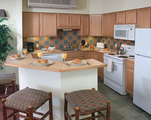 A well equipped kitchen with a breakfast bar and a refrigerator.