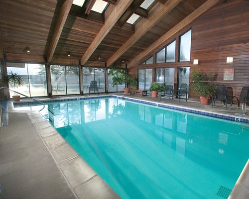 Indoor swimming pool with patio chairs and outside view.