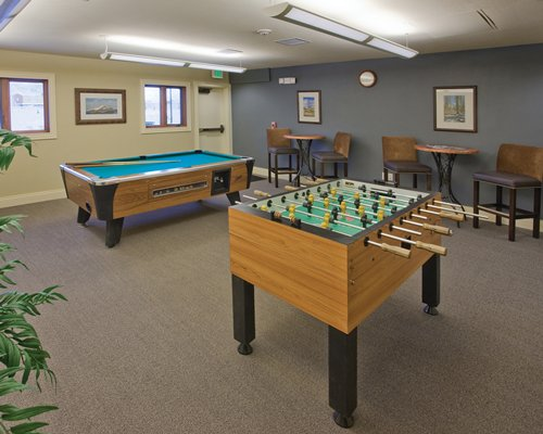 An indoor recreational area with pool table and table soccer.