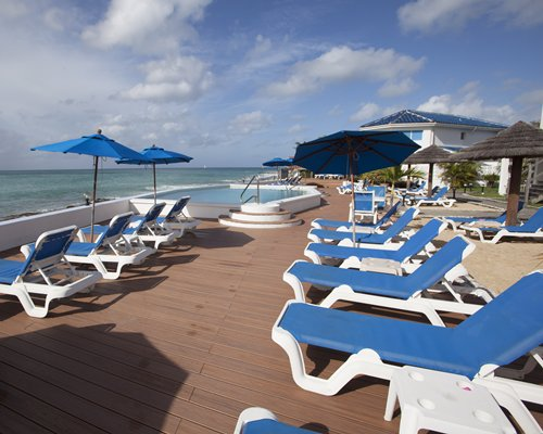 View of chaise lounge chairs and sunshades alongside beach.