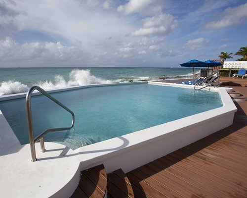 An outdoor pool with chaise lounge chairs alongside the ocean.
