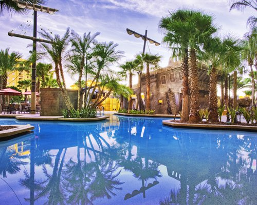 An outdoor swimming pool alongside palm trees.