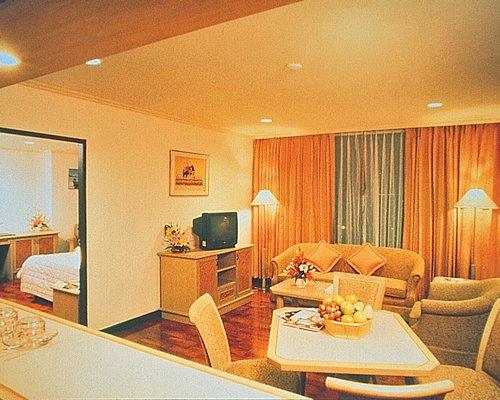 An open plan furnished living room with wooden dining area pull out sofa and television.