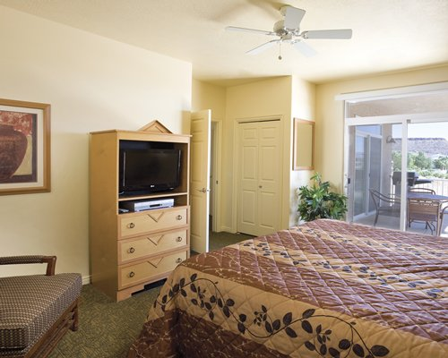 A well furnished bedroom with television and patio.