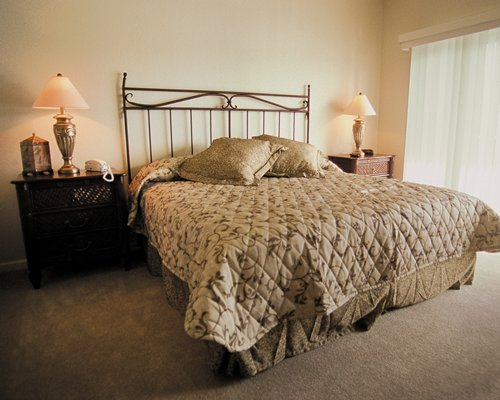 A well furnished bedroom with king bed and outside view.