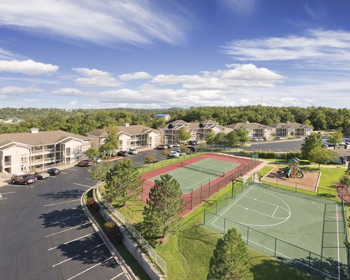 An aerial view of an outdoor tennis court basketball court and kids playscape.