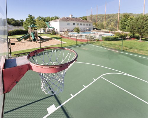 An outdoor basketball court alongside kids playscape.