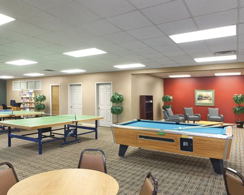 A well furnished indoor recreation room with a pool table and ping pong courts.