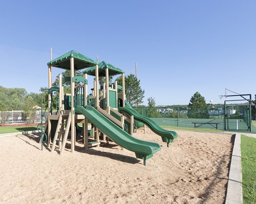 An outdoor playscape alongside tennis court.