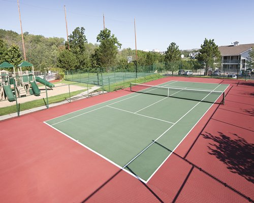 An outdoor tennis and volleyball court with a parking lot.