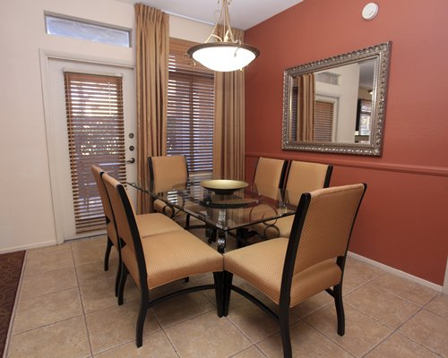 A well equipped dining area with glass top table.
