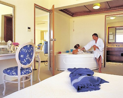 A well furnished bedroom with couple bathing in a hot tub.