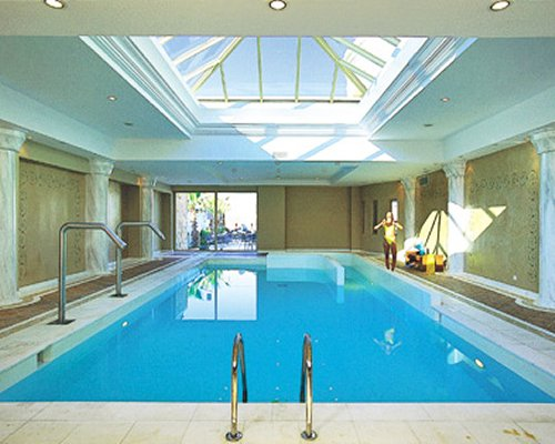 An indoor swimming pool with an outside view.