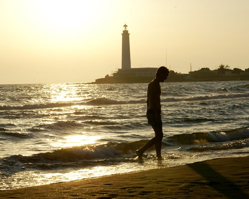View of the lighthouse with a man walking on the beach.