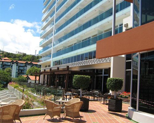 Exterior view of Pestana Carlton Tower Suites with outdoor restaurant.