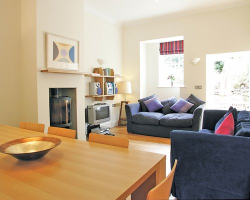 An open plan living and dining area with double pull out sofas and a television.