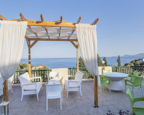 A balcony with patio furniture alongside the sea.