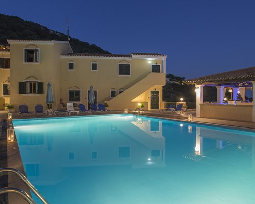 A night view of an outdoor swimming pool alongside Corfu Residence resort.