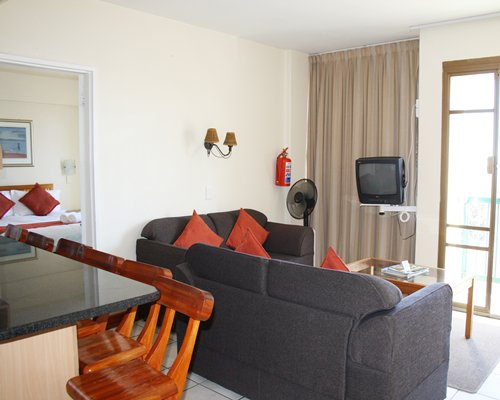 A well furnished living area with television and pullout sofa alongside breakfast bar.