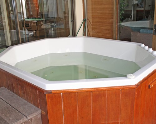 Indoor hot tub with a view of recreation room with pool table.