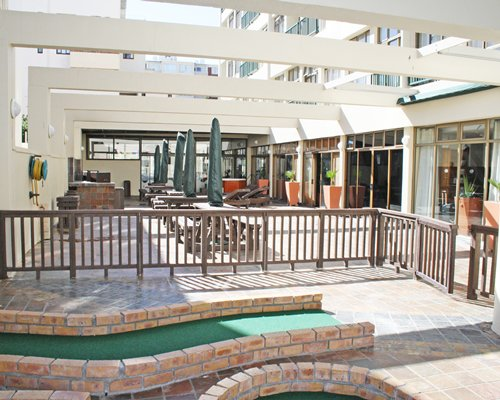 An outdoor lounge area alongside multi story resort condos.