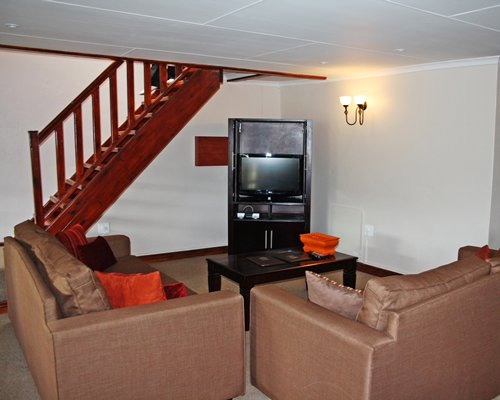 Furnished living room with a television alongside staircase.