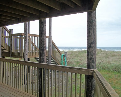Balcony with a wooden stairway and beach view.