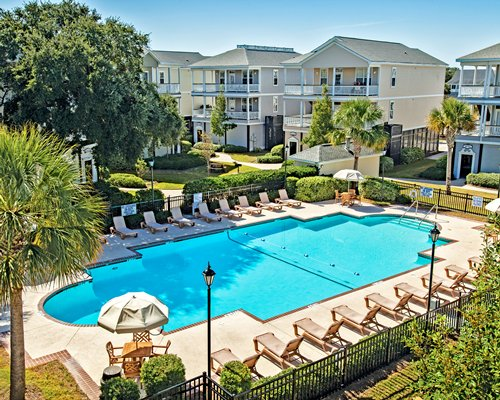A scenic outdoor swimming pool with chaise lounge chairs alongside multi story condos.