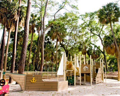 An outdoor children's play area surrounded by trees.