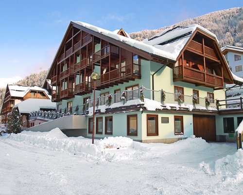 Exterior view of Domina Home Parco Dello Stelvio resort covered in snow.