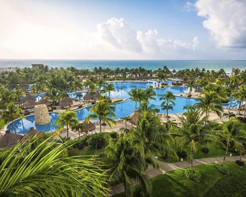A scenic view of the Mayan Palace at Vidanta Riviera Maya resort alongside a waterfront.
