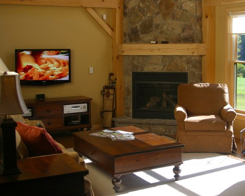 A well furnished living room with television fireplace and outside view.