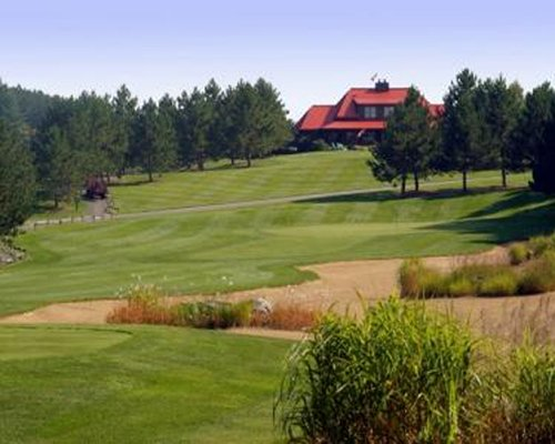 Golf course surrounded by wooded area with view of a unit.