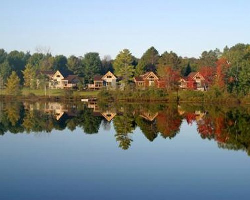 A lake view of the resort surrounded by wooded area.