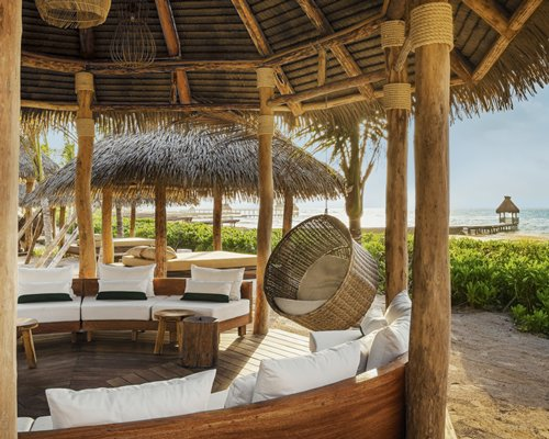 A beach with thatched sunshades chaise lounge chairs and wooden pier.